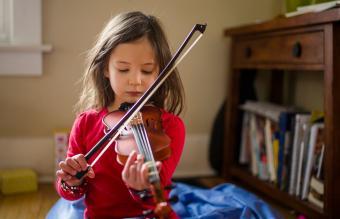 Focused girl practicing violin
