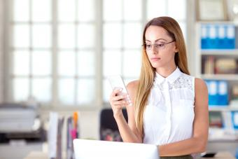 Serious businesswoman using mobile phone