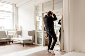Rear view of businessman looking in mirror