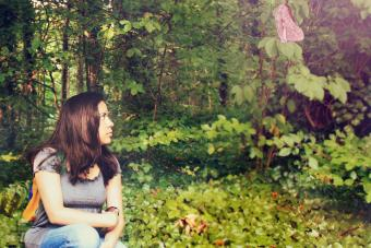 Woman sitting on ivy-covered soil looking at a butterfly