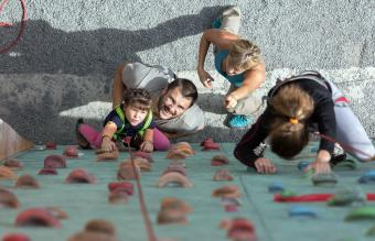 girl doing first steps on climbing wall