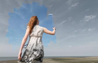 woman painting grey sky blue