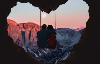 Couple on swing contemplating the mountains
