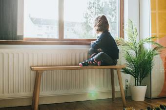 Little Girl sitting on a Bench by a sunny Window