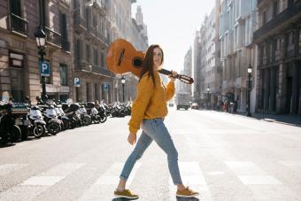 Red-haired woman with a guitar on zebra crossing