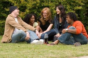 Group of friends sitting on grass and laughing