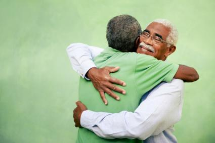 Elderly men hugging