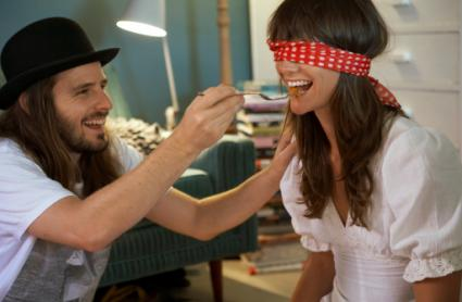 man feeding blindfolded woman