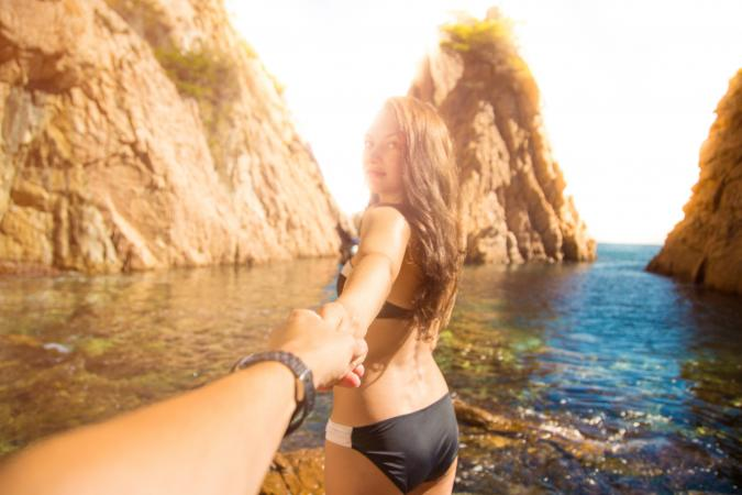 Girl holding boyfriend's hand in Mediterranean Sea