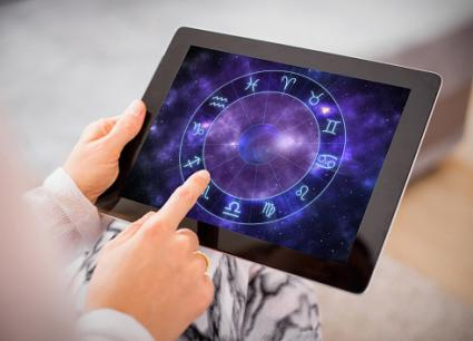 Woman reading horoscopes on tablet