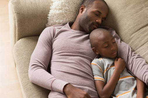 Father and son sleeping on sofa