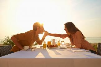 Woman feeding man at sunset dinner outdoors