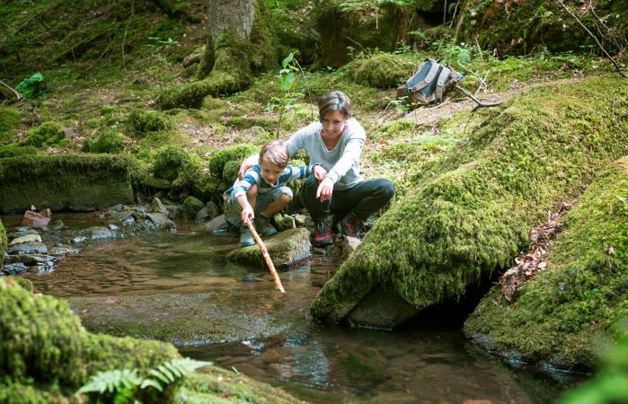 Mother and son crouching at edge of a brook