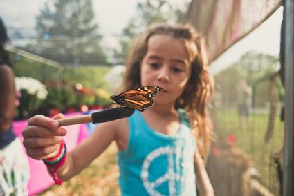 Inquisitive Libra girl with monarch butterfly
