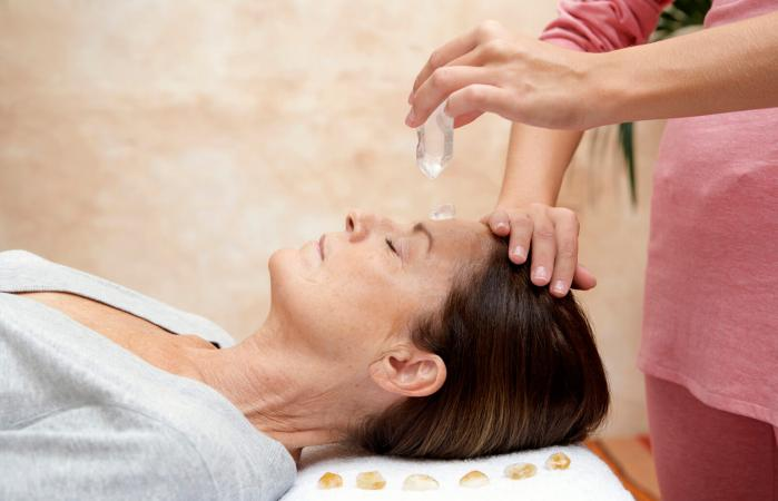 Woman receiving crystal healing treatment