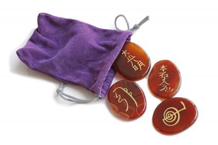 Reiki symbols on stones with purple bag
