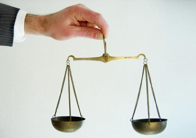 Man balancing set of scales