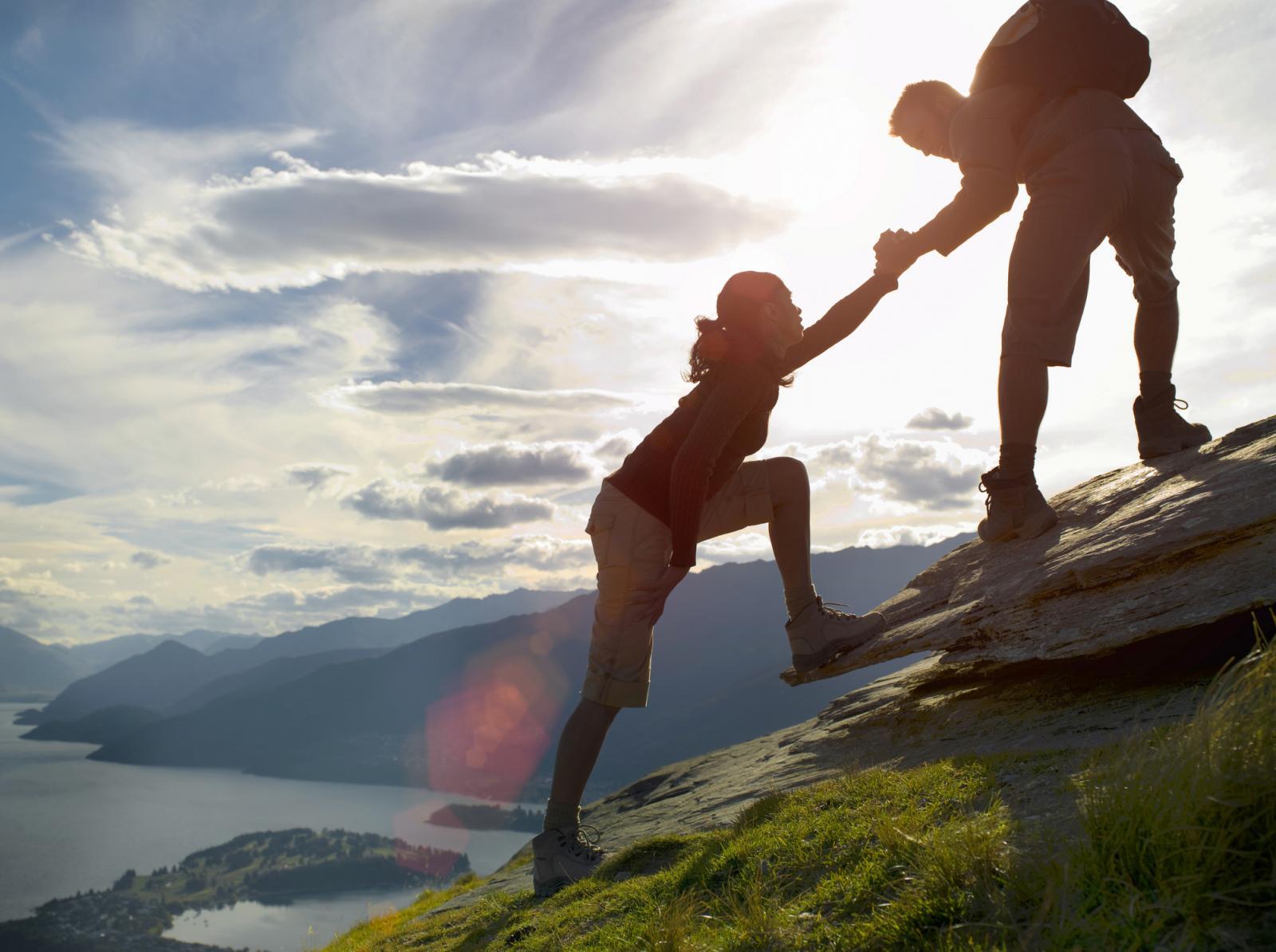 Silhouette of couple climbing hillside near a lake