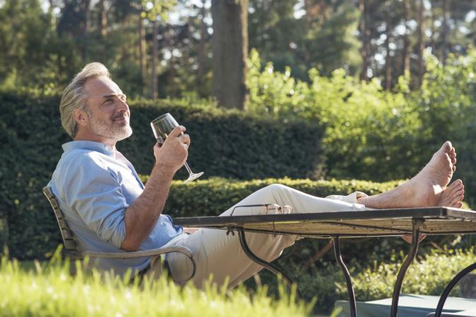 man in garden drinking wine