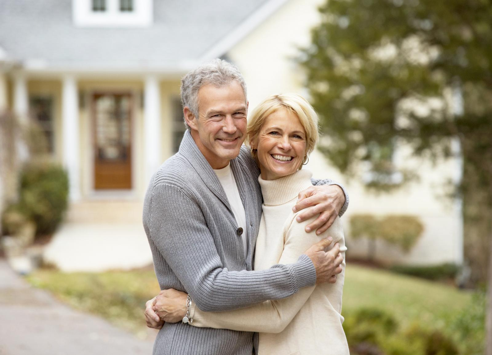 Happy couple hugging outside house