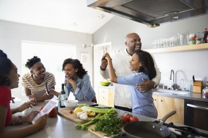 Parents dancing and cooking with children in kitchen