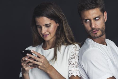 Jealous man watches partner texting