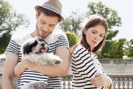 happy man with puppy and upset woman
