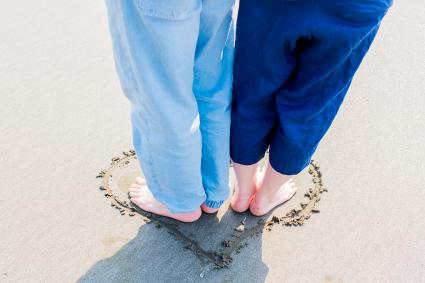 couple standing in heart on the beach