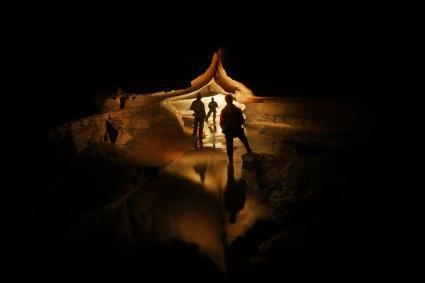 Friends standing in dark cave