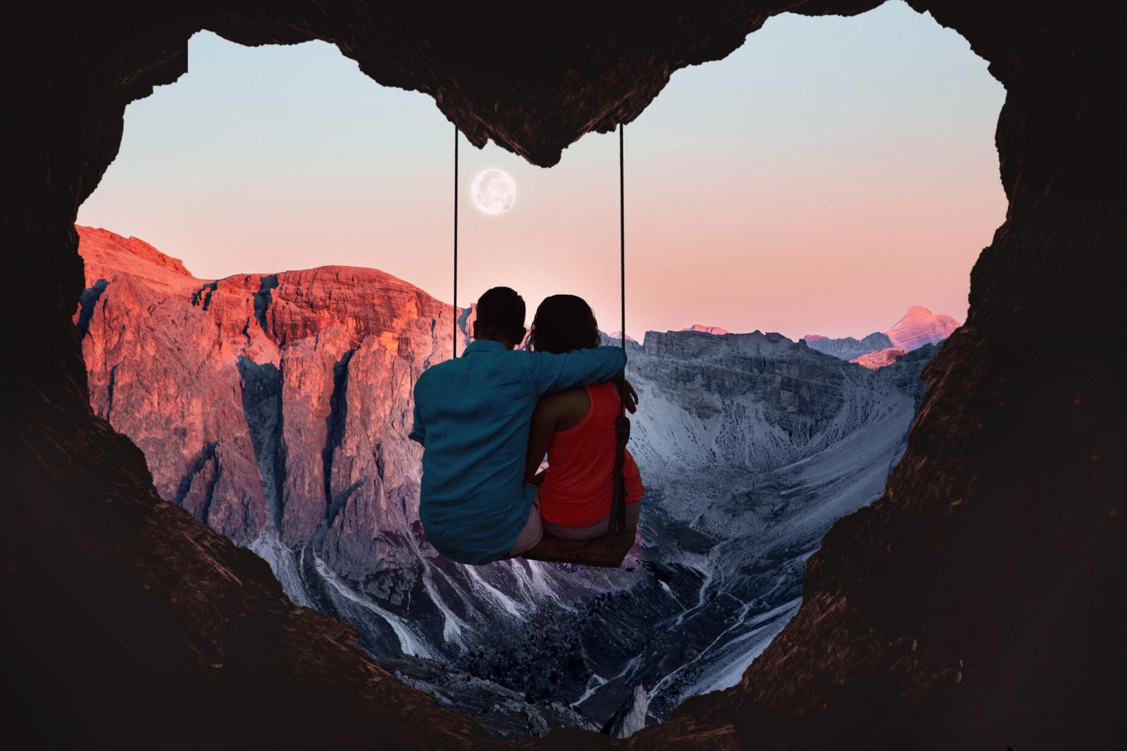Couple on swing from a heart shape cave and full moon