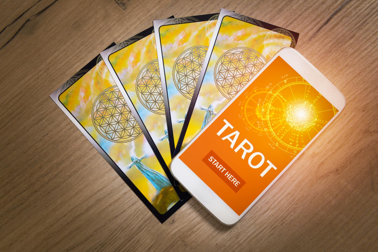 Tarot cards and smartphone with modern fortunetelling application