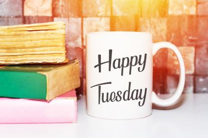 Happy tuesday word on white morning coffee cup and books