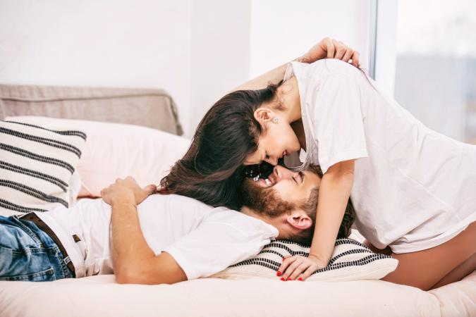 Happy couple man and woman at home in bedroom