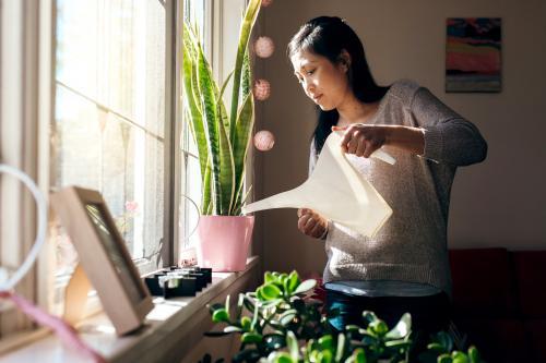 Asian woman watering green plants