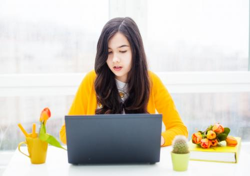 Girl wearing yellow sitting with laptop