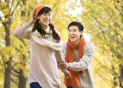 Young Couple Playing in a Park in Autumn