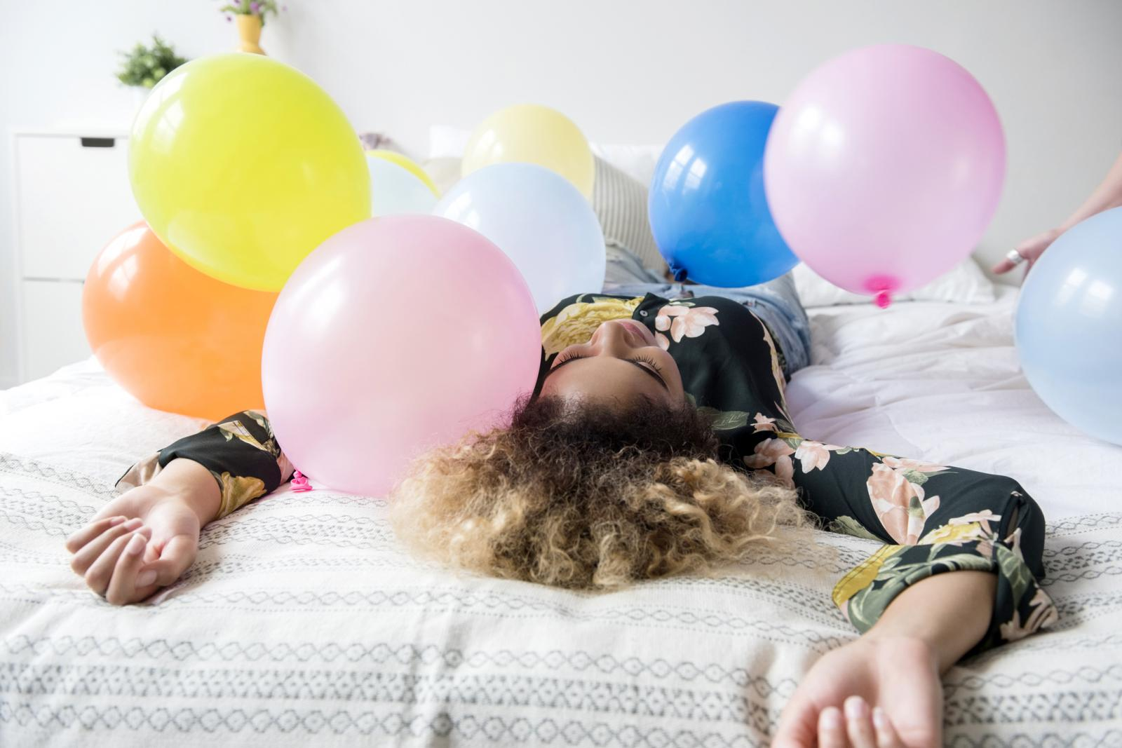 Mixed Race woman sitting on bed covered with balloons