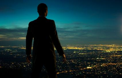 Man looking over cityscape at night