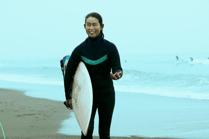 Woman on beach with surfboard
