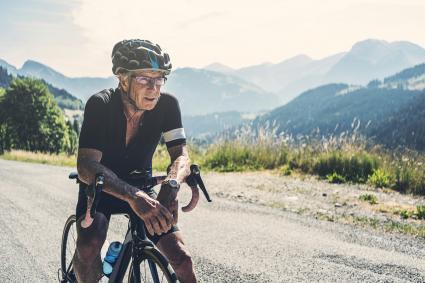 Senior man resting on mountain bike trail