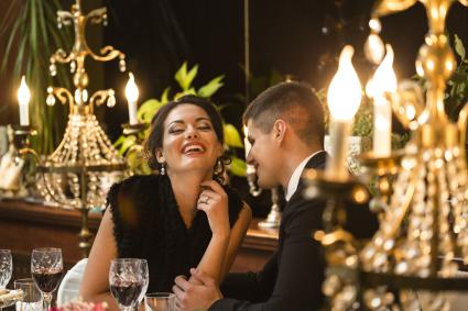 Woman laughing with man during dinner date