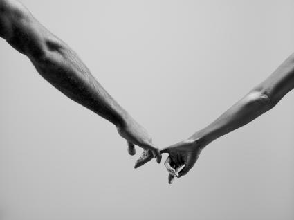 Man and woman linking little fingers together