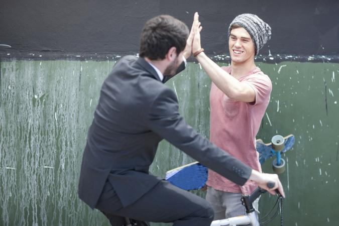 Skateboarder and businessman in suit high five