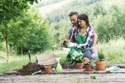 Man and woman repotting plants enjoying each other