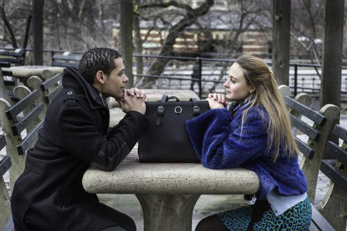 Man and woman staring at each other across table outdoors