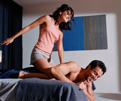 Woman sitting on man's back on bed laughing