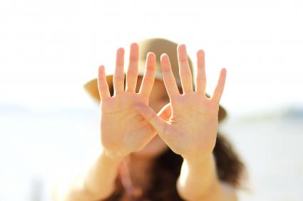 Young woman reaching hands in front of face