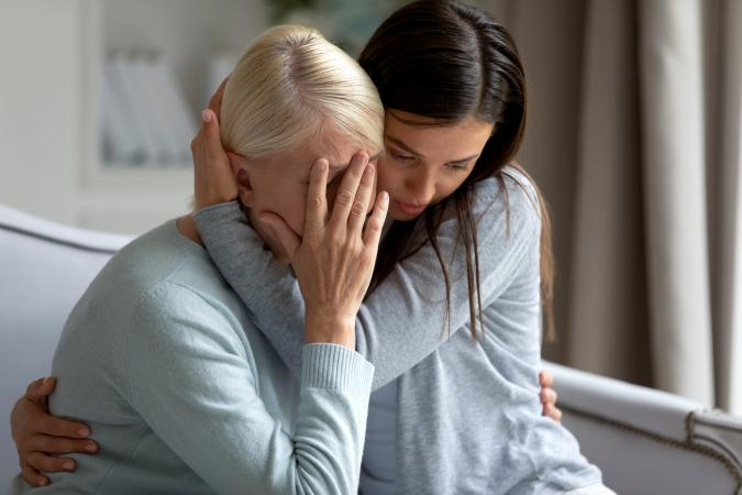 Empathic young lady embracing and soothing elder lady