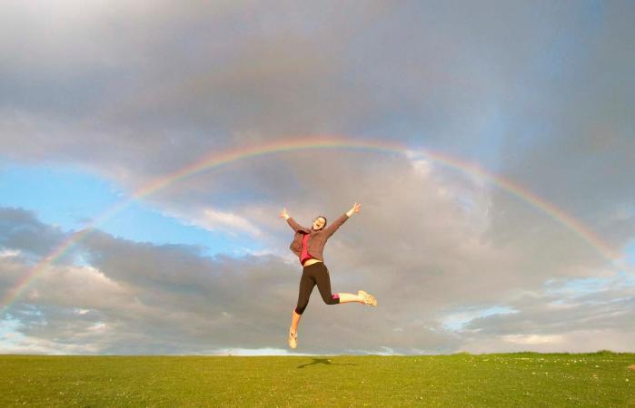 hiker jumping mid air below rainbow