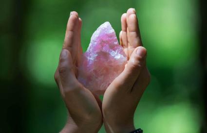 Hands holding a rose quartz